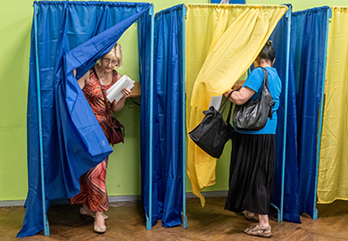 Voters enter and exit voting booths in the colors of the Ukrainian flag.