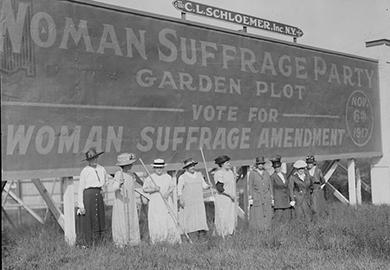 Suffragists stand in front of a billboard supporting the women's suffrage amendment in 1917.
