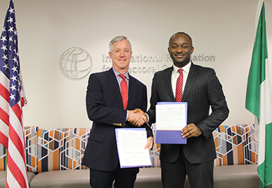 Banbury and Itodo shake hands after signing the Memorandum of Understanding, which formalized their organizations' partnership.