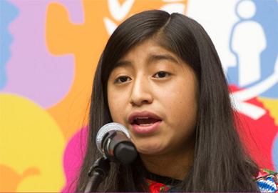 A girl speaks at a microphone. © United Nations