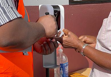 A poll worker applies indelible ink to a voter's finger during the Turks and Caicos Islands' 2021 general elections.
