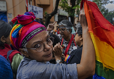 A person holds a rainbow flag during a march about LGBT rights in India's electoral processes. © Amitava Chandra