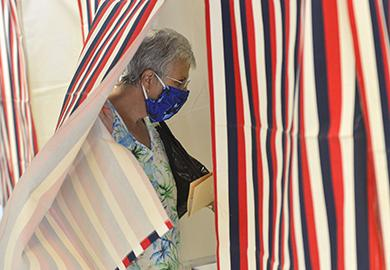 A voter wearing a face mask enters a polling booth during the New Hampshire state primaries on September 8, 2020. © Kristopher Radder/The Brattleboro Reformer via AP