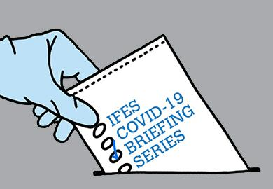 """Illustration of a voter wearing latex gloves and casting a ballot that reads """"IFES COVID-19 BRIEFING SERIES"""" with a check next to """"BRIEFING"""""""