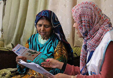 A Tunisian woman invites an outreach ambassador into her home to discuss the 2018 municipal elections.