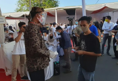 A poll worker checks participant temperatures as they take part in a voting simulation in Indonesia. © Association for Elections and Democracy