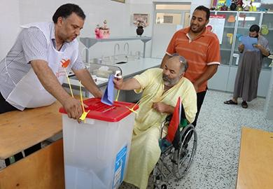 A man who uses a wheelchair casts his ballot on Election Day in Libya in July 2012.