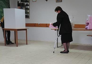 A voter with a physical disability casts a ballot during Serbia's 2020 elections.