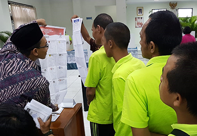 Voters at a psychiatric hospital in Jakarta study the ballot on Election Day.