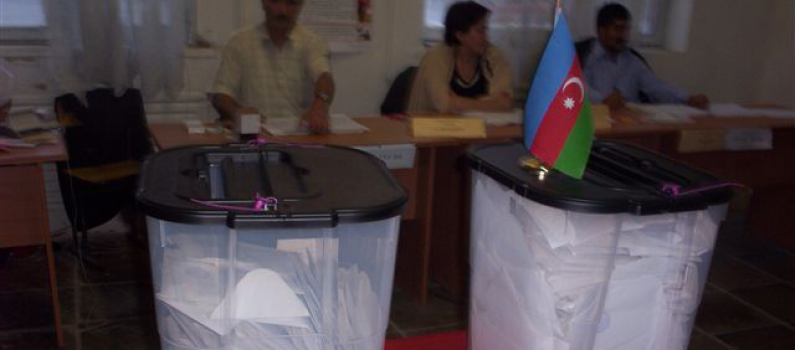 Two ballot boxes from a previous election, one of which has the Azerbaijani flag