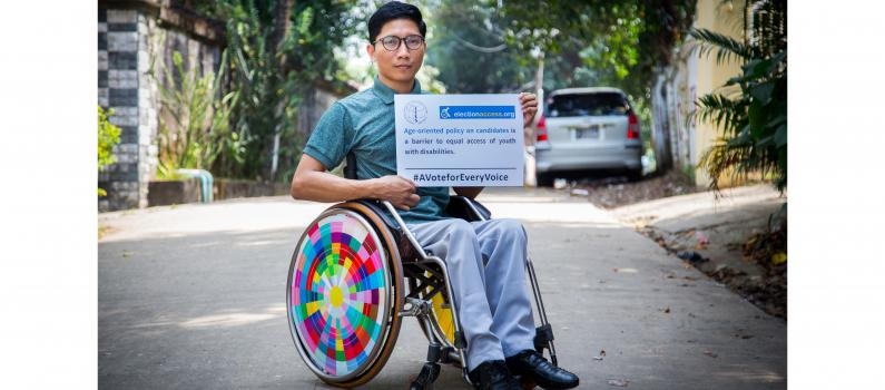 """A man using a wheelchair holds a sign that says, """"Age-oriented policy on candidates is a barrier to equal access of youth with disabilities."""""""