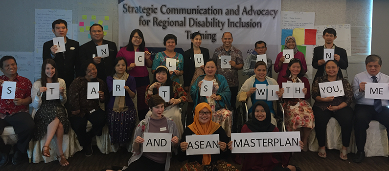"Workshop participants and organizers hold signs that say, ""Inclusion starts with you, me and ASEAN masterplan"""