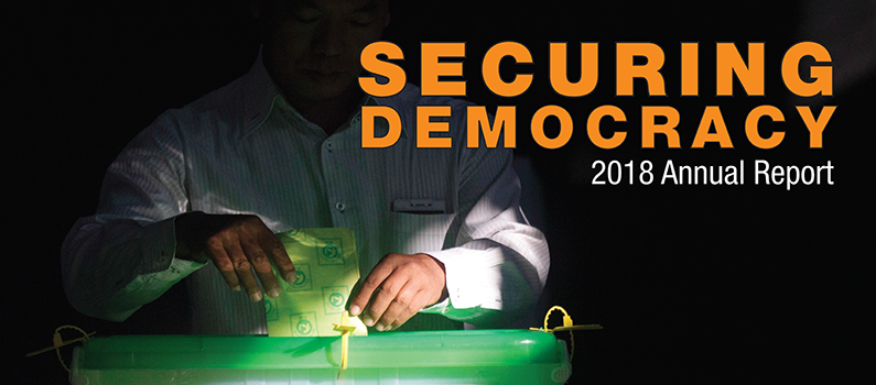 """Cover of """"Securing Democracy: IFES' 2018 Annual Report"""" (background: A voter casts his ballot at a polling station in Yangon, Myanmar, during the 2018 by-elections.)"""