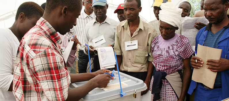 Observers watch as a filled ballot box is sealed at a polling station in Harare.