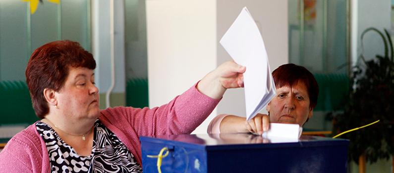 Two Bosnian women cast their ballots at a polling station during the 2010 elections.