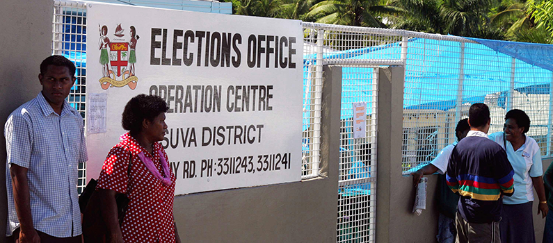 People stand outside a caged election office in Suva, Fiji, Friday, May 5, 2006.