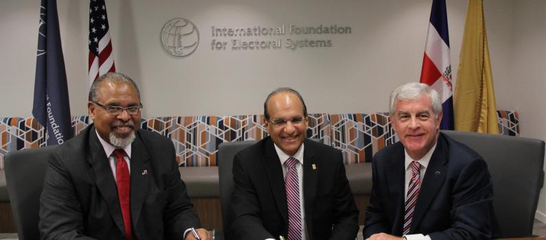 IFES Board Chairman Ken Blackwell, JCE President Julio Cesar Castaños Guzmán and IFES President and CEO Bill Sweeney sign the MoU.