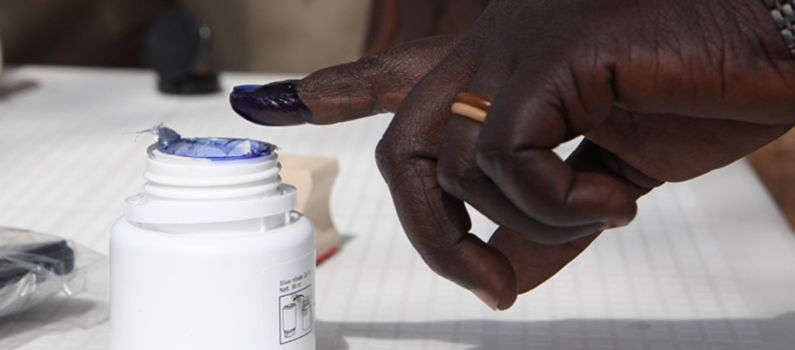 A finger dipped in ink hovers over an bottle of indelible ink.