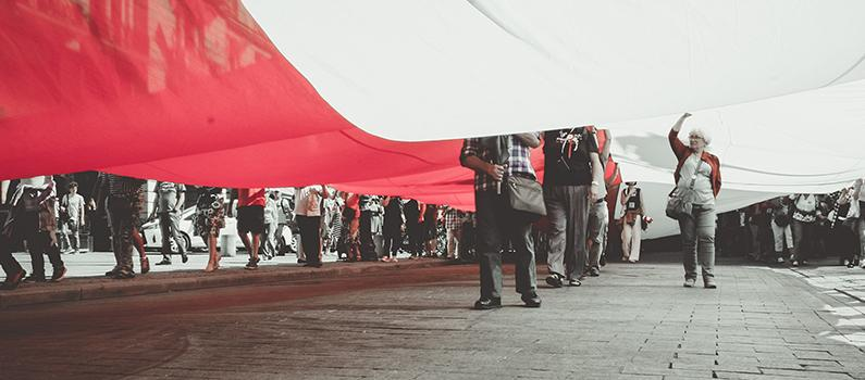 Protesters march under a Polish flag.