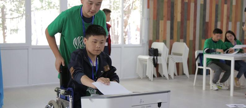A student in Kyrgyzstan inserts a ballot into a scanner during a mock election at an IFES Democracy Camp.