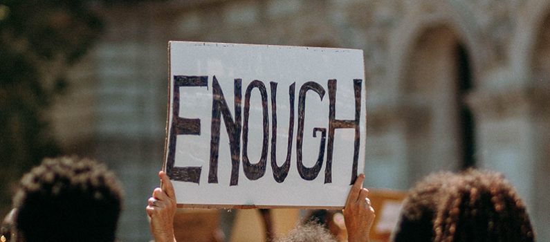 A sign being held up reads: enough