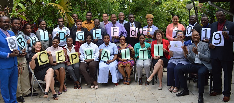"Participants and facilitators from the TtF workshop hold up signs that spell out, ""BRIDGE FdF 2019 CEP Haiti USAID"""