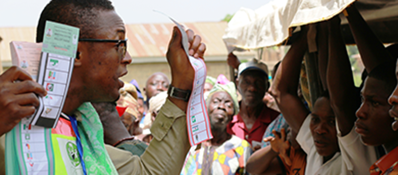 A presiding officer in Ekiti state explains to voters how to mark a ballot during Nigeria's 2015 general elections.