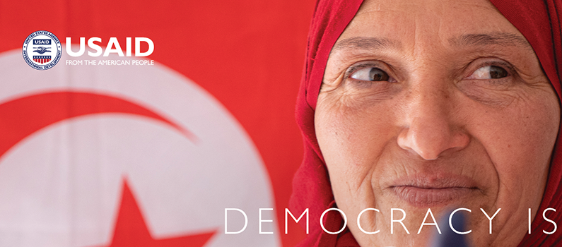 "Selma Sbissi holds up an inked finger. USAID logo, Text: ""Democracy Is"""