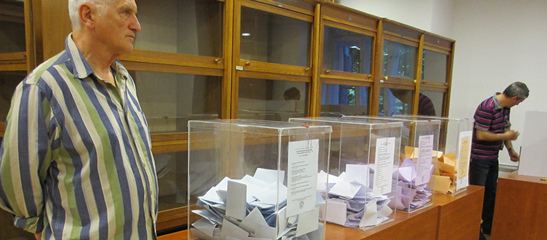 A Serbian man stands next to the a series of ballot boxes