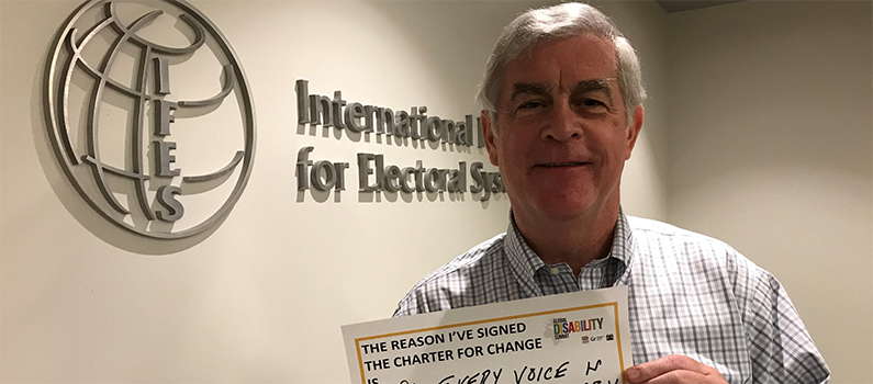 """IFES President Bill Sweeney holds a sign that says, """"The reason I've signed the Charter for Change is so every voice is heard and every vote is counted."""""""