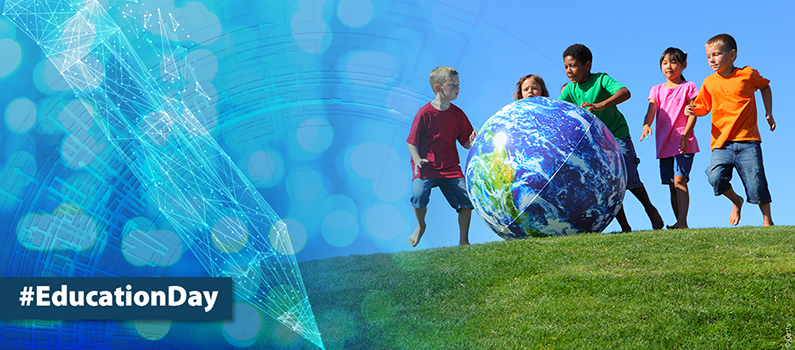 Children roll an inflatable globe across a field. Text: #Education Day © UNESCO