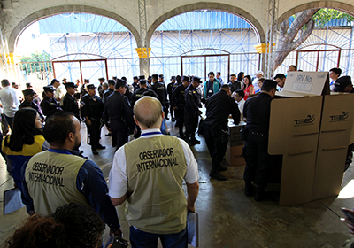 International observers watch police officers vote in a polling station.