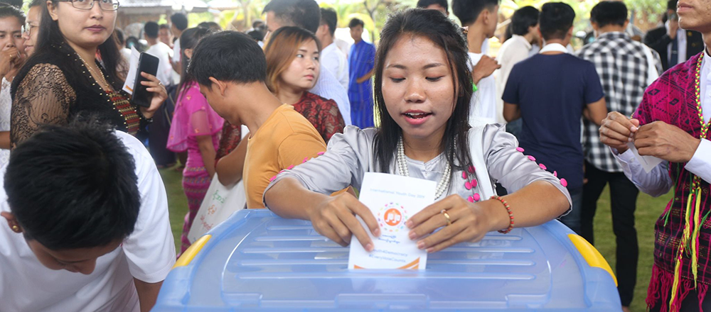 A young participant learns how to properly cast a ballot at the UEC mock polling station.
