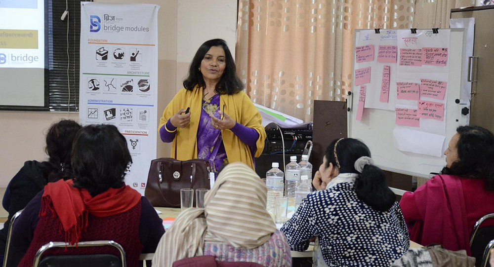 Regmi explains the important role of women leaders to political party members during a BRIDGE workshop on gender and elections.